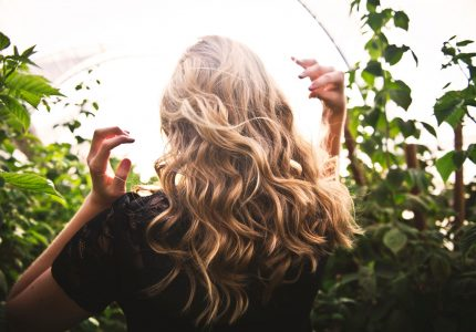 blonde-haired-woman-standing-between-green-plants-1049687